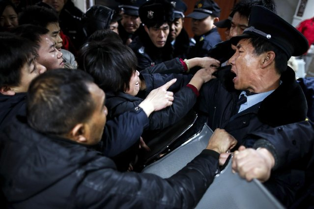 Relatives try to push past security guards at a hospital where those injured by a stampede are being treated in Shanghai, China, Thursday January 1, 2015. (Photo by Ng Han Guan/AP Photo)