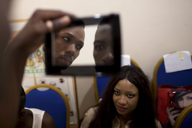 Models look at themselves in a mirror before the Festi'Bazin runway show in Bamako, Mali, October 16, 2015. (Photo by Joe Penney/Reuters)