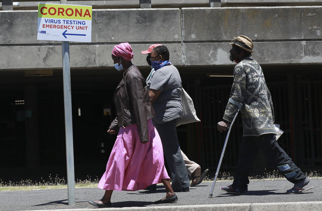 People pass a sign at Groote Schuur Hospital in Cape Town, South Africa, indicating a COVID testing station Tuesday, December 29, 2020. South African President Cyril Ramaphosa has declared the wearing of masks compulsory and has reimposed a ban on the sales of alcohol and ordered the closure of all bars and beaches as part of new restrictions to help the country battle a resurgence of the coronavirus, including a new variant. (Photo by Nardus Engelbrecht/AP Photo)