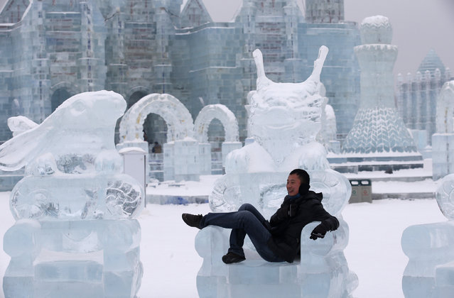 A visitor takes a picture with an ice sculpture ahead of the 31st Harbin International Ice and Snow Festival in the northern city of Harbin, Heilongjiang province, January 4, 2015. (Photo by Kim Kyung-Hoon/Reuters)