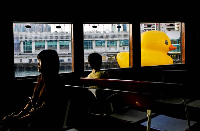 A giant rubber duck created by Dutch artist Florentijn Hofman is seen on May 29, 2013 from the window of a star ferry along Hong Kong's Victoria Habour. Since 2007, the 54-foot tall Rubber Duck has traveled to various cites including Osaka, Sydney, Sao Paulo and Amsterdam. (Photo by Vincent Yu/Associated Press)