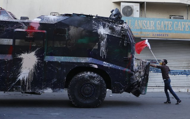A protester, holding a Bahraini flag, confronts a riot police armoured personnel carrier in an attempt to stop it from entering the village of Bilad Al Qadeem south of Manama, January 6, 2015. Bahraini police fired rubber bullets and tear gas to scatter protesters who gathered outside the home of Sheikh Ali Salman, a Shi'ite Muslim opposition leader on Monday, witnesses said, after he was remanded in custody for a further 15 days. (Photo by Hamad I. Mohammed/Reuters)