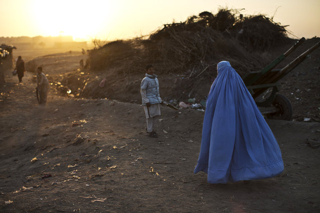 A woman, right, walks by Afghan refugee boys playing in a slum that hosts Afghan refugees and internally displaced Pakistanis from tribal areas on the outskirts of Islamabad, Pakistan, Thursday, January 1, 2015. (Photo by Muhammed Muheisen/AP Photo)