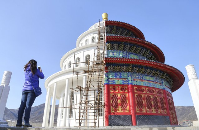 A woman takes pictures with her mobile phone at a building, which is made by half of a replica of the Qinian Hall of the Temple of the Heaven (R) and half of a western building, at a studio for productions of films and television shows on the outskirts of Shijiazhuang, Hebei province, China, December 3, 2015. (Photo by Reuters/Stringer)