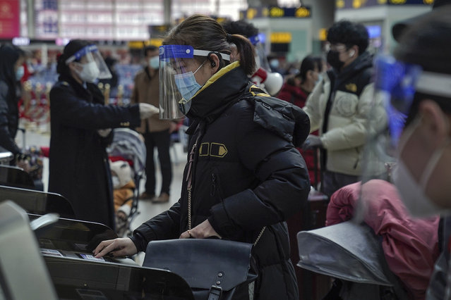 A woman wearing a face mask and face shield to help curb the spread of the coronavirus prepares to board her train at the South Train Station in Beijing, Thursday, January 28, 2021. (Photo by Andy Wong/AP Photo)