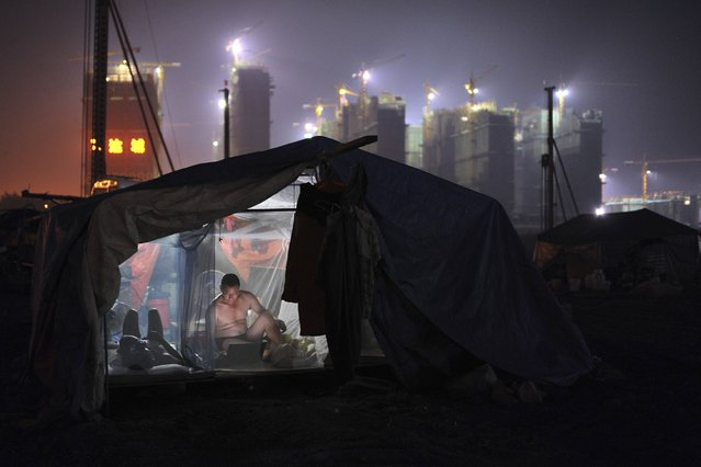 A worker uses a laptop inside his dormitory near a residential construction site in Hefei, Anhui province August 6, 2014. (Photo by Jianan Yu/Reuters)