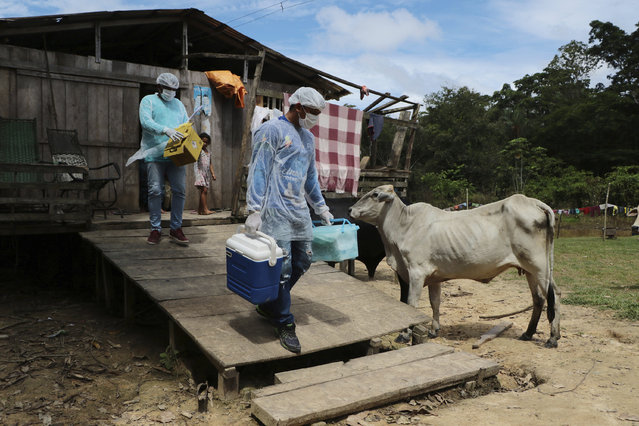 Health workers Diego Feitosa Ferreira, 28, right, and Clemilton Lopes de Oliveira, 41, leave a home after a resident denied to be vaccinated against the new coronavirus, in the Capacini community, along the Purus river, in the Labrea municipality, Amazonas state, Brazil, Friday, February 12, 2021. Navigating complex waterways to reach remote communities in Brazil's Amazon is only the first challenge for the healthcare workers vaccinating Indigenous and riverine people against COVID-19. (Photo by Edmar Barros/AP Photo)