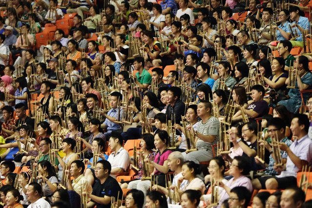 Some 5,390 participants play a song with Anklungs, Indonesian traditional bamboo musical instruments, during a performance in an attempt to break the Guinness World Record for the largest number of people playing Angklung, on July 1, 2013. (Photo by Jason Lee/Reuters)