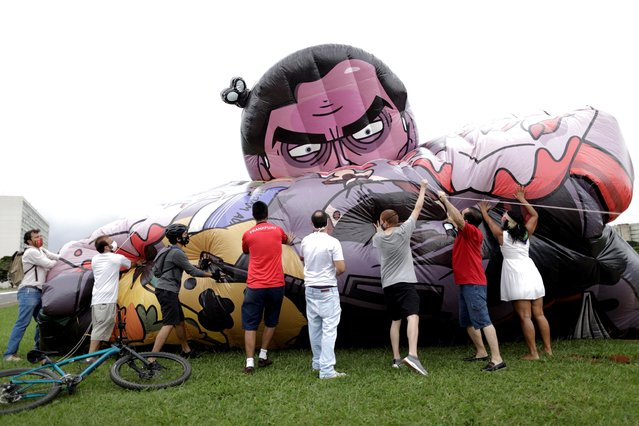 Activists and members of social organizations inflate a doll depicting Brazil's President Jair Bolsonaro during a protest demanding his impeachment in Brasilia, Brazil, February 21, 2021. (Photo by Ueslei Marcelino/Reuters)