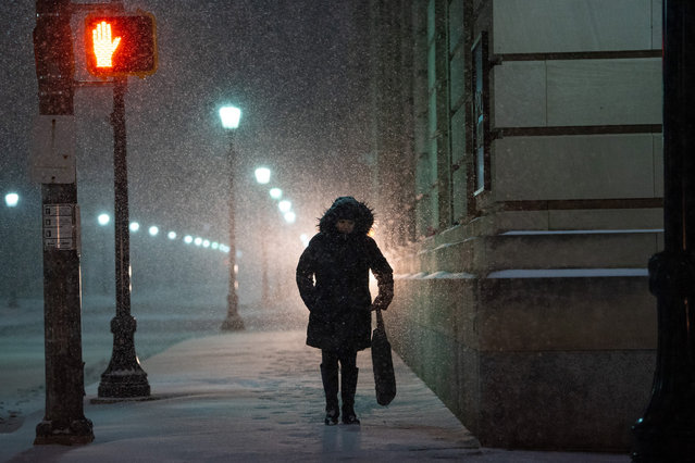 Car headlights illuminate a woman walking through city streets as snow accumulates on December 16, 2020 in Wilkes Barre, Pennsylvania. Winter Storm Gail is expected to bring more than a foot of snow in parts of the Northeast. (Photo by Mark Makela/Getty Images)
