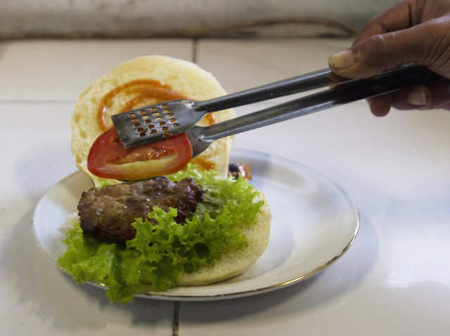 A chef prepares a cobra meat burger at a Chinese restaurant in the ancient city of Yogyakarta April 1, 2011. Snake hunters catch about 1,000 cobras from Yogyakarta, Central Java and East Java provinces each week to harvest their meat for burgers, priced at 10,000 rupiah ($1.15) each, as well as satay and other dishes. Some customers said they believe cobra meat can cure skin diseases and asthma, and increase sexual virility. (Photo by Dwi Oblo/Reuters)