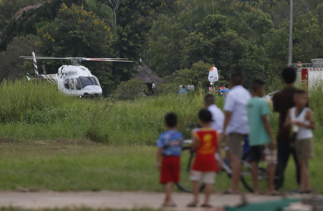 A helicopter believed to be carrying one of the boys rescued from the flooded cave lands in Chiang Rai as divers continue to extract the remaining boys and their coach trapped at Tham Luang cave in the Mae Sai district in Chiang Rai province, northern Thailand, Tuesday, July 10, 2018. Thai Navy SEALs say all 12 boys and their coach were rescued from the cave, ending an ordeal that lasted more than 2 weeks. (Photo by Vincent Thian/AP Photo)