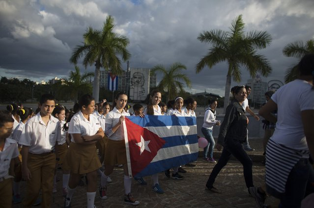 Students hold Cuba's national flag at the memorial of Jose Marti on Revolution Square in Havana January 28, 2015. Cuban youths gathered at the memorial to celebrate the 162nd birthday of national independence hero and poet Marti. Marti, who was forced to live most of his life in exile due to his opposition to Spanish colonial rule, launched an invasion of Cuba for its independence in 1895. He was killed the same year. (Photo by Alexandre Meneghini/Reuters)