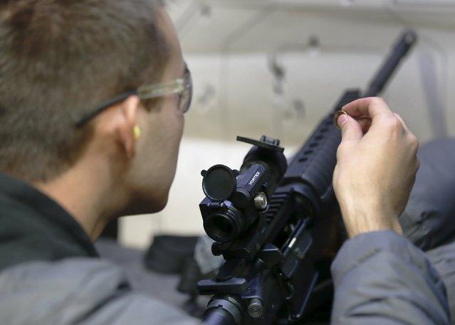 Alec Murrary adjusts the sights of an AR-15 assault rifle at the Ringmasters of Utah gun range, in Springville, Utah on December 18, 2015. (Photo by George Frey/Reuters)