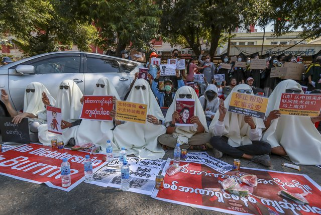 Hooded demonstrators display placards accusing China for supporting Myanmar's military during a protest against the recent coup outside the Chinese Embassy in Yangon, Myanmar, Thursday, February 11, 2021. (Photo by AP Photo/Stringer)