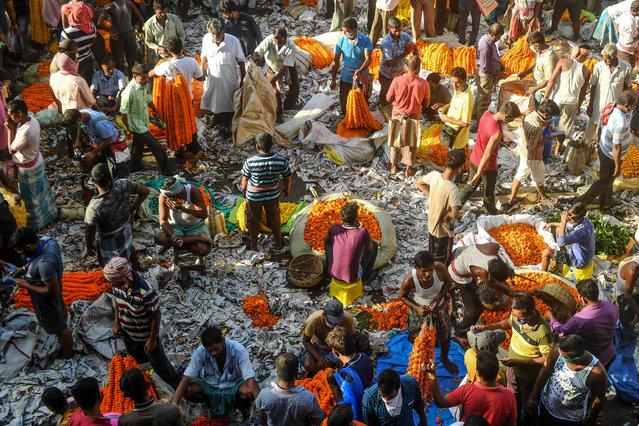 Hindu devotees and flower vendors gather at the main flower wholesale market of Kolkata on September 17, 2020. (Photo by Dibyangshu Sarkar/AFP Photo)