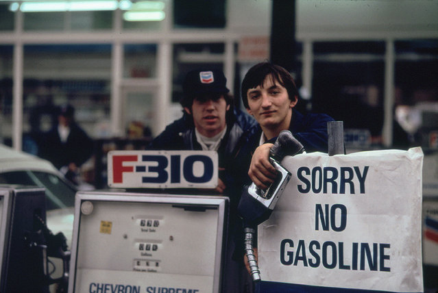 """Gas station attendants peer over their """"Out of Gas"""" sign in Portland, one day before the state's requested Saturday closure of gasoline stations, November 1973. (Photo by David Falconer/NARA via The Atlantic)"""