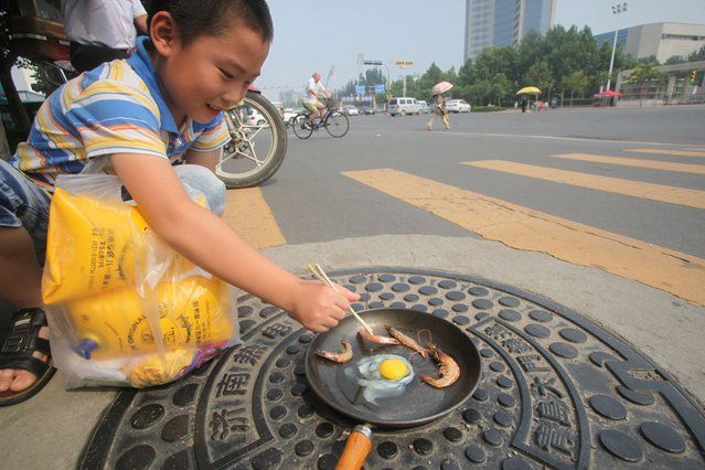 A boy cooks an egg and shrimps on a metal manhole cover on a road in Jinan, China, on August 2, 2013. China Meteorological Administration issued a Level Two national heat alert on Tuesday, the most severe heat alert ever issued. (Photo by Feature China/Barcroft Media)