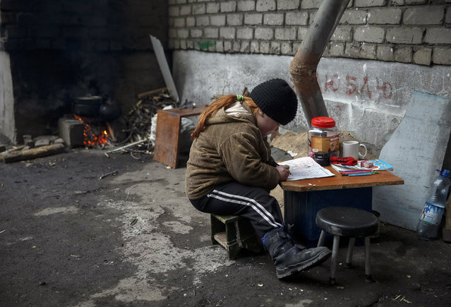 A child draws near her house in Debaltseve, eastern Ukraine, February 5, 2015. (Photo by Gleb Garanich/Reuters)