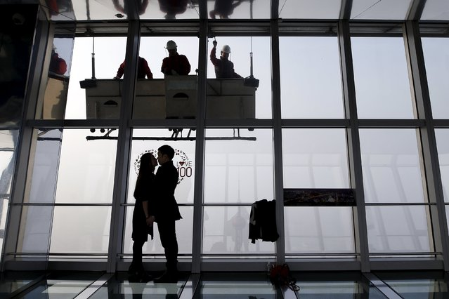 A couple embraces while workers clean the exterior of the Shanghai World Financial Center skyscraper amid heavy smog at the financial district of Pudong in Shanghai, China, December 25, 2015. (Photo by Aly Song/Reuters)