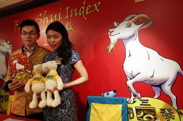 """Wand bearer"" Marco Yau (L) and ""Wicked witch of the East"" Cherry Ma, both associated analysts from CLSA, pose with toy goats and a 2015 Feng Shui Index, during a news conference in Hong Kong February 5, 2015. Asian brokerage CLSA published on Wednesday its Feng Shui Index, a tongue-in-cheek forecast for the Hang Seng and sector outlooks for Hong Kong and China. (Photo by Bobby Yip/Reuters)"
