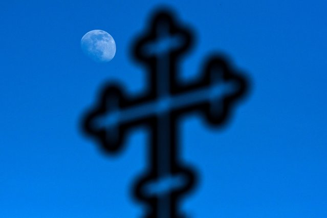 The moon is pictured behind a cross in Moscow on March 25, 2021. (Photo by Kirill Kudryavtsev/AFP Photo)