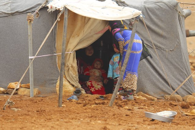Internally displaced Syrians rest inside a tent at a refugee camp in the Hama countryside, Syria January 1, 2016. (Photo by Ammar Abdullah/Reuters)