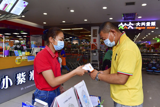 In this photo released by Xinhua News Agency, a resident goes through health screening to enter a supermarket in Ruili, southwestern China's Yunnan Province, on April 1, 2021. COVID-19 cases in the southwestern Chinese city of Ruili bordering on Myanmar have now topped 100 on Monday, April 5, 2021. That comes as authorities have launched an aggressive campaign to vaccinate all 300,000 residents of the city, whose outbreak is something of an anomaly in a country that has all-but eliminated local transmission of the virus.(Photo by Chen Xinbo/Xinhua via AP Photo)