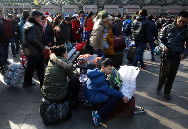 A woman and boy wait as Chinese travelers queue up at the main entrance of the Beijing railway station in Beijing, Friday, February 13, 2015. Millions of Chinese will be traveling to their hometowns to celebrate the Lunar New Year on Feb. 19 this year which marks the Year of the Sheep on the Chinese zodiac. (Photo by Andy Wong/AP Photo)