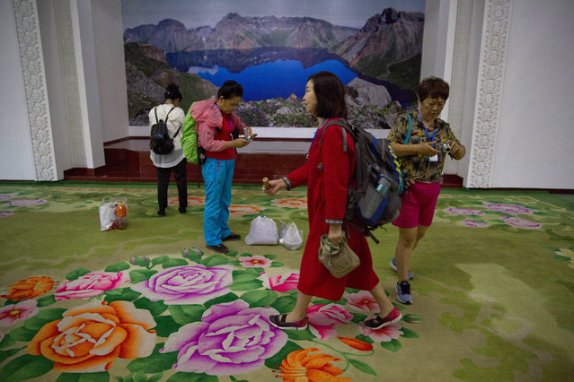 In this Friday, August 17, 2018, photo, Chinese tourists arrive at the Pegaebong hotel lobby which displays a giant photo of the caldera on Mount Paektu in the town of Samjiyong in North Korea. (Photo by Ng Han Guan/AP Photo)