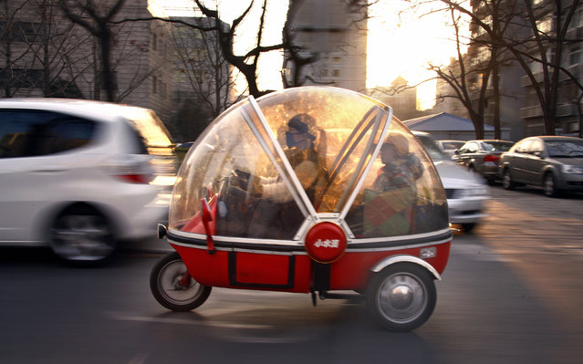 A woman and her son sit inside the capsule of an electric tricycle as they drive along a main road in central Beijing March 15, 2012. (Photo by David Gray/Reuters)