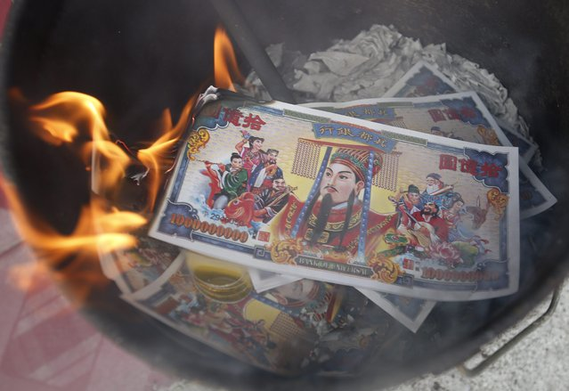 Paper money, called spirit money, is burnt in a bucket by an ethnic-Chinese Thai family in a traditional Chinese New Year ritual, believing that they will be passed onto their ancestors, at the front entrance of their shop-house home in Bangkok, Thailand, 18 February 2015. Food is laid on the table at the front of the house in a tradition to placate the mythical beast who is said to come on the first day of every New Year. (Photo by Barbara Walton/EPA)