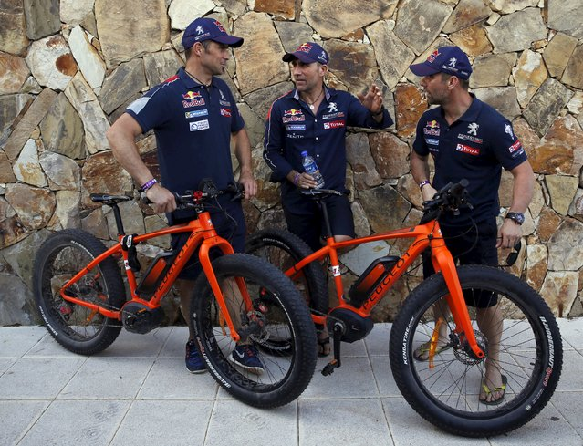Members of the Peugeot Rally Dakar Team France's drivers Cyril Despres, Stephane Peterhansel and Sebastien Loeb (L-R) talk as they pose with Peugeot bicycles at the bivouac of the Dakar Rally 2016 in Salta, Argentina, January 10, 2016. (Photo by Marcos Brindicci/Reuters)