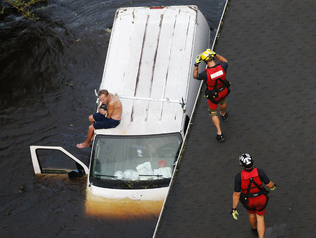U.S. Coast Guard rescue swimmer Samuel Knoeppel, center, and Randy Haba, bottom right, approach to Willie Schubert of Pollocksville, N.C., on a stranded van in Pollocksville on Monday, September 17, 2018, in the aftermath of Hurricane Florence. (Photo by Steve Helber/AP Photo)