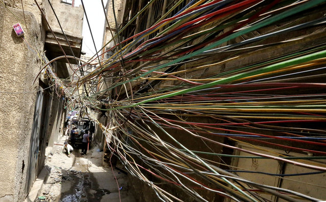 A picture taken on April 27, 2021, shows the electrical wires running between homes in the capital Baghdad's Murabaa neighbourhood. Between January and March alone, the interior ministry recorded 7,000 fires, the deadliest of which erupted on Sunday in a Covid-19 hospital in Baghdad. Eighty-two people died and 100 others were injured in the inferno, which sparked shock and outrage in the country. Baghdad, a sprawling metropolis of 10 million people, has the tragic distinction of being the Iraqi city hit by the most fires every year. (Photo by Sabah Arar/AFP Photo)