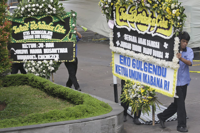"Wreaths of condolence for attack victims, one with the words ""Let's Not Fight Each Other"", are brought to the area outside the Starbucks cafe where Thursday's attack occurred in Jakarta, Indonesia, on Friday, January 15, 2016. (Photo by Tatan Syuflana/AP Photo)"