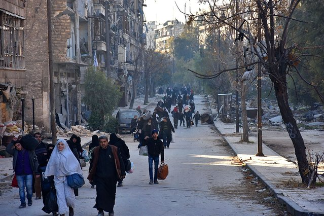 Syrian residents fleeing the violence in the eastern rebel- held parts of Aleppo evacuate from their neighbourhoods through the Bab al- Hadid district after it was seized by the government forces, on December 7, 2016. In the face of a blistering assault by forces loyal to President Bashar al- Assad, the rebels were reported to have retreated from all of Aleppo' s Old City, the latest in a string of territorial losses. (Photo by George Ourfalian/AFP Photo)
