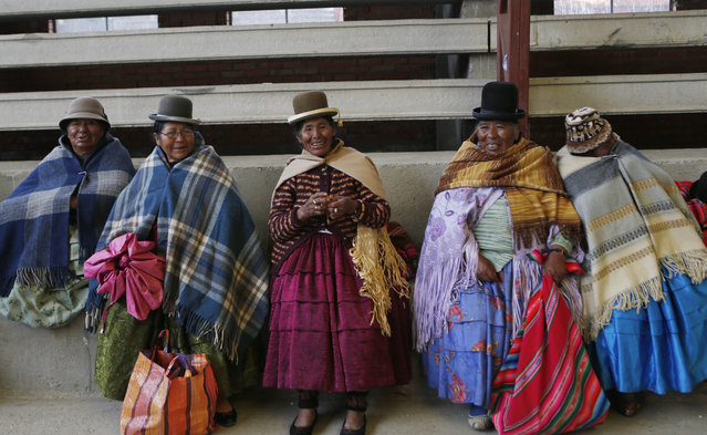 """In this February 11, 2105 photo, elderly Aymara indigenous women rest on the bleachers after playing handball in El Alto, Bolivia. Known in the Aymara language as """"awichas"""", or grandmothers, the women pull sports jerseys over their long-sleeved blouses and ruffled skirts to play the game. (Photo by Juan Karita/AP Photo)"""