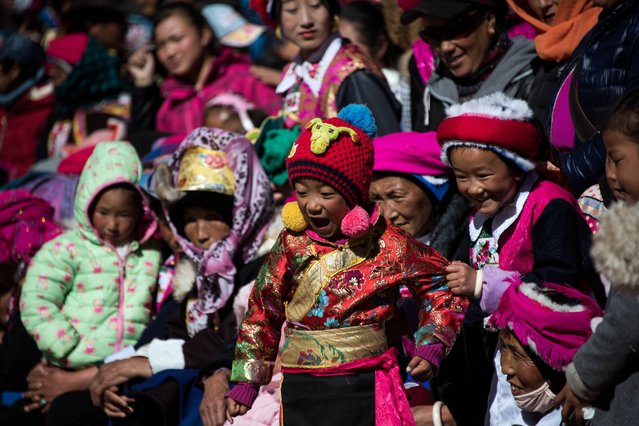 This picture taken on January 5, 2016 at the Ganden Sumtsenling Monastery in Shangri-La, Diqing Tibetan Autonomous Prefecture of southwest China's Yunnan Province, shows Children in traditional Tibetan clothes watching the Cham dance during the Gedong festival.  Thousands of metres above sea level, high on the Tibetan plateau, hundreds of Tibetan Buddhist devotees in brilliant hues of pink and blue gathered for the Gedong festival. Lamas young and old mixed with festival-goers wearing traditional garb to watch the religious Cham dance at the Ganden Sumstseling monastery in Shangri-La. (Photo by Johannes Eisele/AFP Photo)