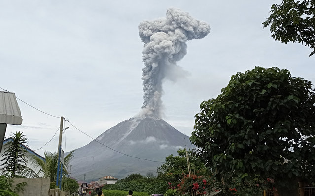 """Mount Sinabung releases volcanic materials during an eruption in Karo, North Sumatra, Indonesia, Friday, May 7, 2021. Sinabung is among more than 120 active volcanoes in Indonesia, which is prone to seismic upheaval due to its location on the Pacific """"Ring of Fire"""", an arc of volcanoes and fault lines encircling the Pacific Basin. (Photo by Sastrawan Ginting/AP Photo)"""