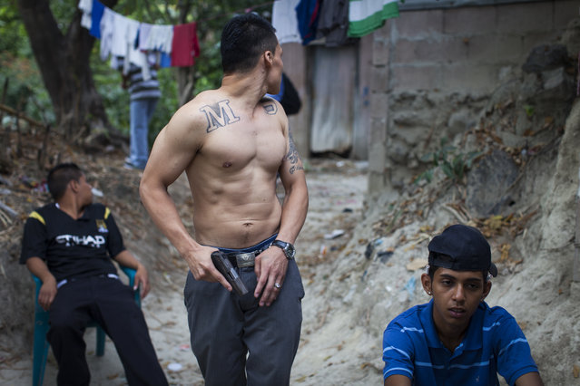 Mara Salvatrucha (MS) gang members show off their weapons in the Las Victorias district of San Salvador. (Photo by Adam Hinton)