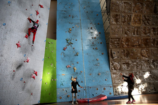 In this Monday, January 18, 2016 photo, Iranian rock climber, Farnaz Esmaeilzadeh, top left, scales a wall in a rock climbing gym as her mother and her friend support her, in the city of Zanjan, some 330 kilometers (207 miles) west of the capital Tehran, Iran. (Photo by Ebrahim Noroozi/AP Photo)