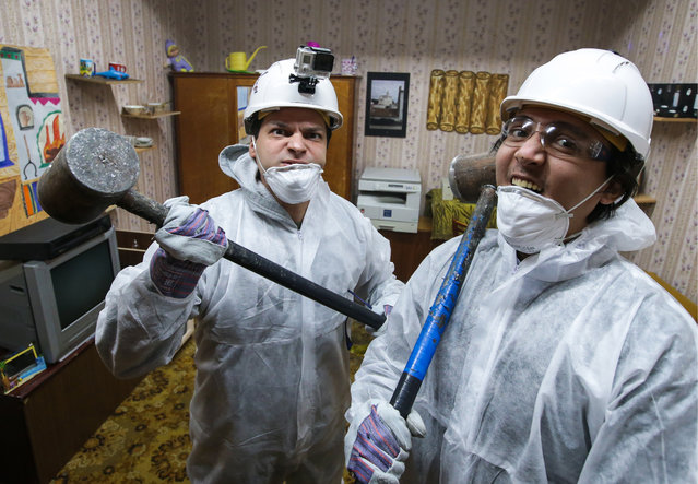 People in hard hats in a rage room in Moscow, Russia on January 27, 2016. The Debosh stress relief service gives its customers an opportunity to smash the rage room up with sledgehammers and bats to relieve stress and tension. (Photo by Artyom Geodakyan/TASS/Barcroft Media)