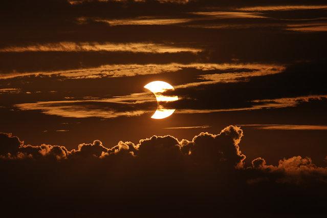 A partial solar eclipse rises behind clouds, Thursday, June 10, 2021, in Arbutus, Md. (Photo by Julio Cortez/AP Photo)