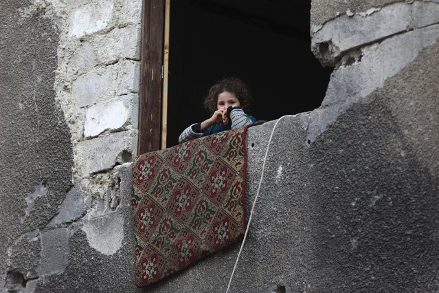A girl looks out the window of a damaged building in Douma, Syria February 3, 2016. (Photo by Bassam Khabieh/Reuters)