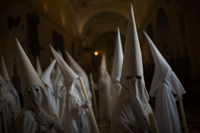 "Penitents wait inside San Francisco church to take part in ""Nuestro Senor Atado a la Columna, Maria Santisima de la Paz y San Juan Evangelista"" Holy Week procession in Arcos de la Frontera, Spain, Tuesday, March 31, 2015. (Photo by Daniel Ochoa de Olza/AP Photo)"