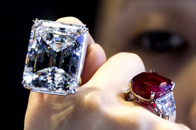 """A model displays both a 100.20 carats (L) and a 25.59 carats, that is known as """"The Sunrise Ruby"""", diamond rings at a pre-auction viewing at Sotheby's in Hong Kong April 3,2015. According to a press release by Sotheby's, the 100.20 carats diamond, described as """"internally flawless"""" by Sotheby's, is expected to fetch between $19-25 million in a New York auction on April 21, 2015. (Photo by Tyrone Siu/Reuters)"""