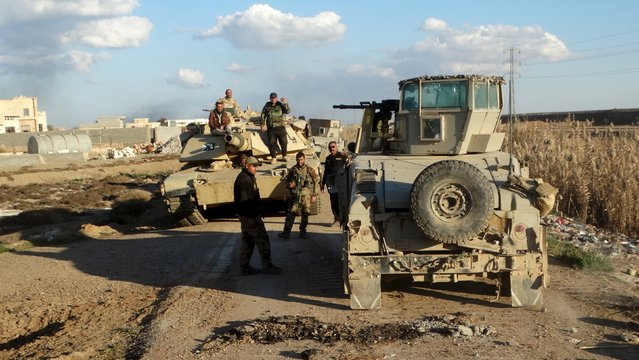 Iraqi security forces gather in Jweba on the eastern fringes of Ramadi, February 8, 2016. Iraqi forces recaptured territory from Islamic State militants on Tuesday which links the recently recaptured city of Ramadi to a major army base in western Iraq, the military said. A statement broadcast on state television said the army, police and counter-terrorism forces had retaken several areas including the town of Husaiba al-Sharqiya, about 10 km (6 miles) east of Ramadi. (Photo by Reuters/Stringer)