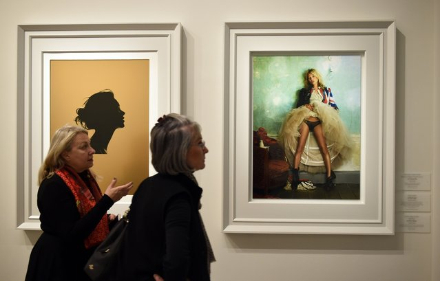"Woman walk by framed photos at the press preview for ""Vogue 100: A Century of Style"" exhibiting the photographs that has been commissioned by British Vogue since it was founded in 1916 at National Portrait Gallery on February 10, 2016 in London, England. (Photo by Stuart C. Wilson/Getty Images)"