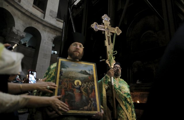 Members of the Greek Orthodox clergy take part in their Palm Sunday procession in the Church of the Holy Sepulchre in Jerusalem's Old City April 5, 2015. (Photo by Ammar Awad/Reuters)
